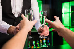 Bartender serving glass of champagne Stock Images