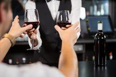 Bartender serving glasses of wine Royalty Free Stock Image
