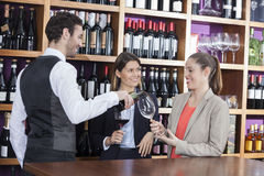 Bartender Serving Red Wine To Female Customers. Smiling bartender serving red wine to female customers at shop Royalty Free Stock Photography