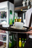 Bartender serving whiskey and a cup of coffee Royalty Free Stock Photos