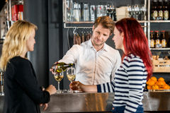 Bartender Serving Wine To Customers In Bar. Young bartender serving wine to female customers at bar counter Royalty Free Stock Images