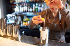 Bartender with shaker preparing cocktail at bar. Alcohol drinks, people and luxury concept - woman bartender with shaker braking egg and preparing cocktail at royalty free stock image