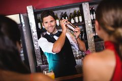 Bartender shaking cocktail in cocktail shaker at bar counter. In nightclub stock photos