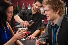 Bartender shaking cocktail friends having drink Stock Photos