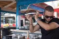 Professional bartender man holding in hands a shaker with a cocktail at the beach bar. 30 may 2018. Albania Durres royalty free stock photo