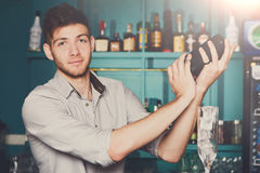 Bartender shaking and mixing alcohol cocktail. Young professional bartender in bar interior shaking and mixing alcohol cocktail with shaker in hands royalty free stock photography