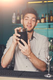 Bartender shaking and mixing alcohol cocktail. Young professional bartender in bar interior shaking and mixing alcohol cocktail with shaker in hands stock photography