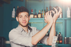 Bartender shaking and mixing alcohol cocktail. Young professional bartender in bar interior shaking and mixing alcohol cocktail with shaker in hands stock images