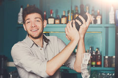 Bartender shaking and mixing alcohol cocktail. Young professional bartender in bar interior shaking and mixing alcohol cocktail with shaker in hands royalty free stock photos
