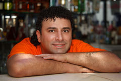 Bartender sits at bar Royalty Free Stock Image
