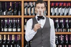 Bartender Smelling Red Wine Against Shelves Stock Photo