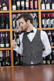 Bartender Smelling Red Wine At Counter Royalty Free Stock Photography