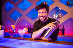 Bartender smiling while holding cocktail shaker. Portrait of bartender smiling while holding cocktail shaker at illuminated bar counter royalty free stock photography