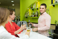 Bartender and smiling women at bar Royalty Free Stock Image