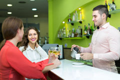 Bartender and smiling women at bar Stock Photo