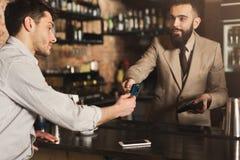 Bartender som accepterar kreditkorten på stångräknaren arkivfoton
