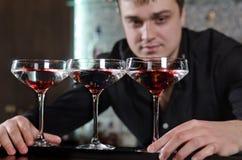 Bartender som arrangera i rak linje tre exponeringsglas av rött vin Fotografering för Bildbyråer