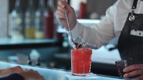 Bartender som dekorerar den röda alkoholiserade coctailen för coctail med bär Arkivbild