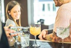 Bartender som f?rbereder coctailar som ut h?ller limefrukt - lyckliga v?nner som v?ntar p? drinkar p? r?knaren i amerikansk st?ng arkivbild