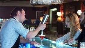 Bartender som förbereder coctailen för en flicka som ser framåtriktat till att sitta på stången Arkivbilder
