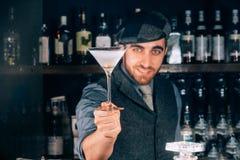 bartender som förbereder och tjänar som den torra martini coctailen i martini exponeringsglas coctail och bartender på stångbakgr Royaltyfri Bild