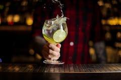 Bartender som gör färgstänk av en Gin Tonic coctail som dekoreras med l royaltyfri bild