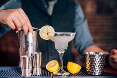 Bartender som garnerar drinken, hällande limefruktmargarita i utsmyckat exponeringsglas på restaurangen arkivfoto