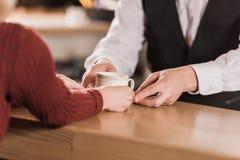Bartender som ger koppen kaffe till klienten royaltyfria bilder