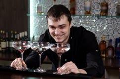 Bartender som grinar, som han spelar med tre coctailar royaltyfria bilder