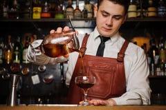 Bartender som häller den nya coctailen i utsmyckat exponeringsglas arkivfoto