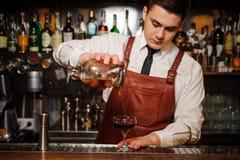 Bartender som häller den nya coctailen i utsmyckat exponeringsglas royaltyfri fotografi