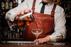 Bartender som häller den nya coctailen i utsmyckat exponeringsglas royaltyfria foton