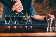 Bartender som häller den starka alkoholdrycken in i små exponeringsglas på stångräknare arkivbild