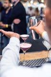 Bartender som häller en coctail in i ett exponeringsglas arkivbild