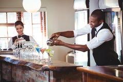 Bartender som häller en drink från en shaker till ett exponeringsglas på stångräknare royaltyfri bild