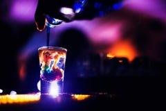 Bartender som häller ett skott av starksprit in i glases Arkivbild
