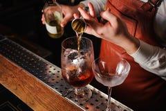 Bartender som häller hård ande in i exponeringsglas i detalj arkivbild