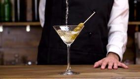 Bartender som häller martini i ett coctailexponeringsglas i ultrarapid lager videofilmer