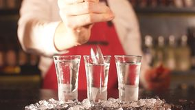 Bartender som häller någon drink från flaskan in i djupfrysta exponeringsglas för skott stock video
