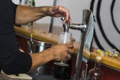Bartender som häller nytt kallt öl från klappet arkivbilder