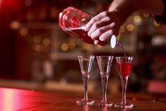Bartender som häller röda skott royaltyfri bild
