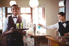 Bartender som rymmer ett portionmagasin med två coctailexponeringsglas royaltyfri bild