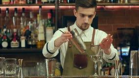 Bartender som skakar coctailen och häller den till ett tomt exponeringsglas på en nattklubb lager videofilmer