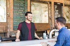 Bartender som tar en beställning från kund royaltyfri fotografi
