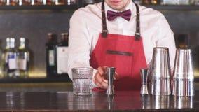 Bartender som tillfogar issmulor in i ett tomt coctailexponeringsglas på stångräknaren på restaurangen stock video