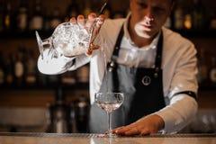 Bartender som tillfogar vodka in i ett coctailexponeringsglas i det mörka ljuset arkivbild