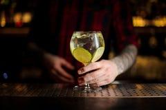 Bartender som tjänar som en Gin Tonic coctail som dekoreras med limefruktskivan arkivfoto