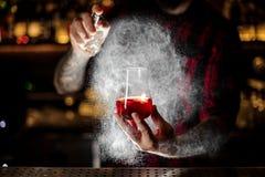 Bartender spraying on the Sazerac cocktail with orange zest royalty free stock photography