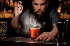 Bartender spraying to the cocktail glass with one big ice cube royalty free stock image