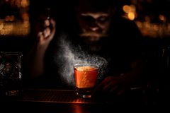 Bartender spraying to the cocktail glass with one big ice cube in the dark stock images